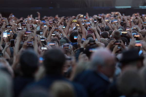 People hold up their mobile phones to film events on stage during a concert by Irish rock band U2 at the Stade de France in Saint-Denis, outside Paris, on July 25, 2017.