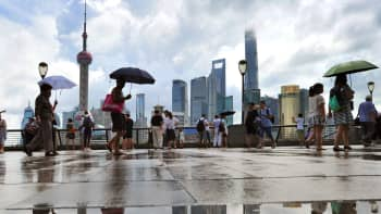 People walk along the Bund on August 16, 2018 in Shanghai, China.