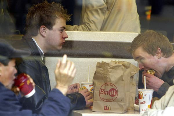 People used to talk to each other when they ate pre-smartphones. Here, two guys eat at a McDonalds restaurant on November 27, 2003 in London.