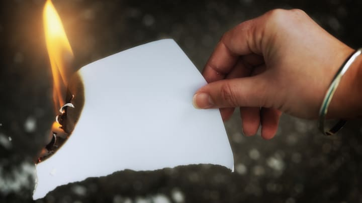 A woman's hand holds a blank piece of paper which is burning up.