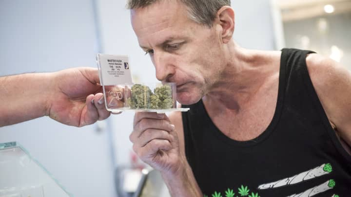 A customer of the medical marijuana dispensary Takoma Wellness Center in Takoma Park, is shown inventory, August 30, 2016.