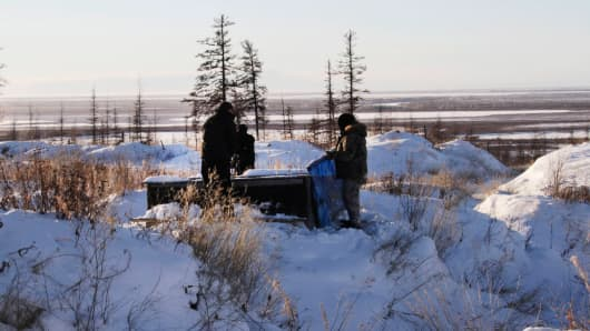 In this photo taken Oct. 27, 2010, Russian scientists Sergey Zimov and his son Nikita Zimov extract air samples from frozen soil near the town of Chersky in Siberia 6,600 kms (4,000 miles) east of Moscow, Russia.