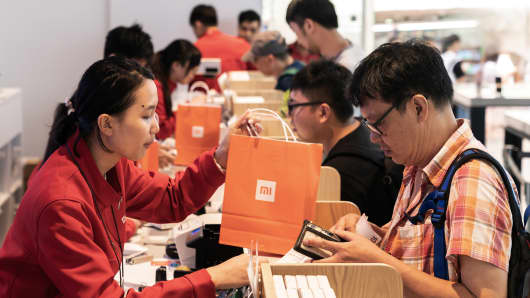 An employee, left, hands a Xiaomi Corp. branded shopping bag to a customer inside a Xiaomi store.