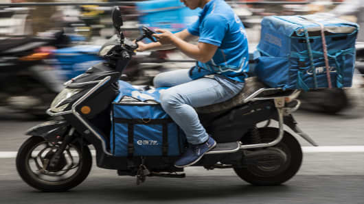 A driver for Ele.me, Alibaba Group Holding Ltd.'s food-delivery platform, rides a motorcycle along a road in Shanghai, China, on Monday, Aug. 20, 2018.