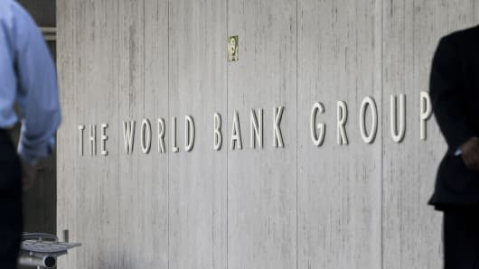 People walk past the headquarters of the World Bank in Washington, D.C., U.S., on Monday April 9, 2012.