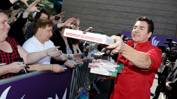 Papa John's Pizza CEO John Schnatter hands out pizza as he arrives at the 47th Annual Academy Of Country Music Awards held at the MGM Grand Garden Arena on April 1, 2012 in Las Vegas