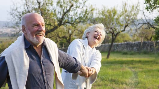 Senior couple walking in rural setting, holding hands, fooling around