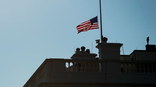The American flag flies at half staff over the White House honoring Senator John McCain in Washington, D.C.