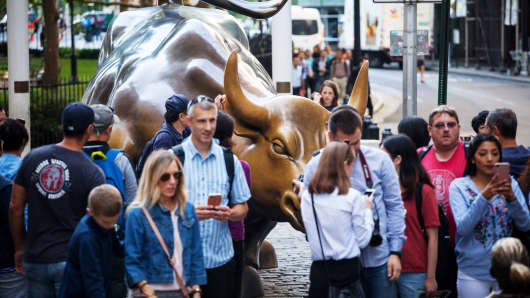 Tourists visit the Charging Bull sculpture near the New York Stock Exchange (NYSE) in New York, Aug. 24, 2018.