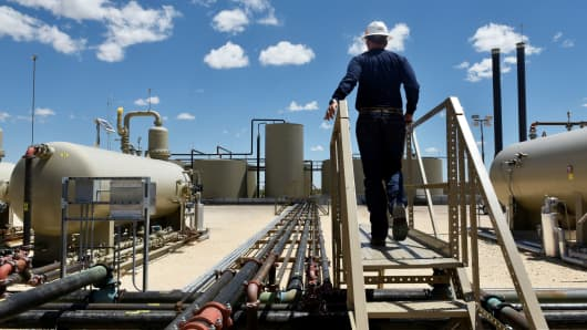 A worker walks through an oil production facility owned by Parsley Energy in the Permian Basin near Midland, Texas, August 23, 2018.