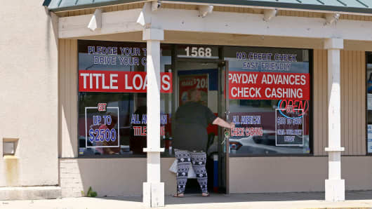 A woman enters an All American Check Cashing location in Brandon, Miss., May 12, 2017.