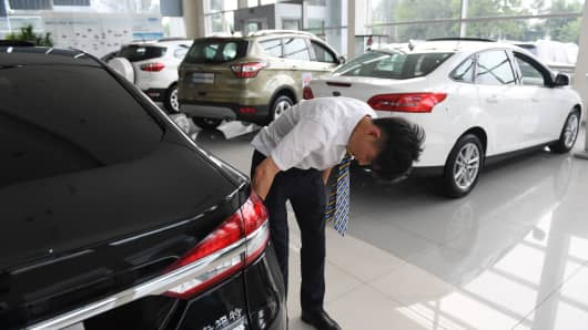 A worker cleans cars at a Ford dealership in Beijing on July 6, 2018. In early July, China said it was 'forced to take necessary countermeasures,' after Washington launched what Beijing called 'the largest trade war in economic history.'