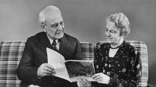 Senior couple reading travel book at home
