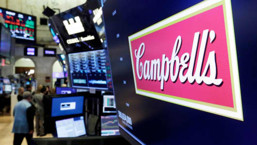The logo for Campbell's Soup appears above a trading post on the floor of the New York Stock Exchange.