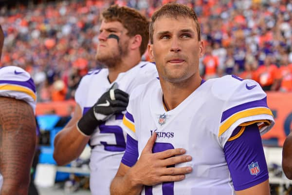 Quarterback Kirk Cousins of the Minnesota Vikings stands on the sideline with teammates during the singing of the National Anthem on August 11, 2018 in Denver, Colorado.