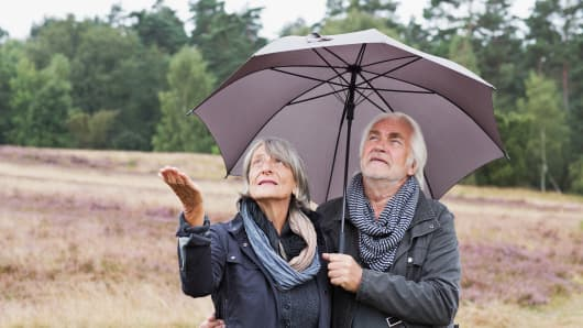 Senior couple under umbrella checking for rain
