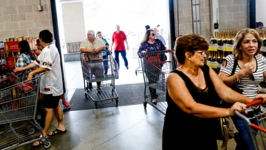 Customers push shopping carts while entering a Costco Wholesale store in Miami, Florida.