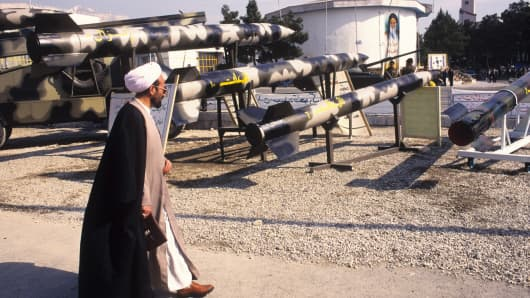 A clergyman walks past a missile display at on the grounds of the International Trade Fair, Tehran, Iran, February 7, 1999.