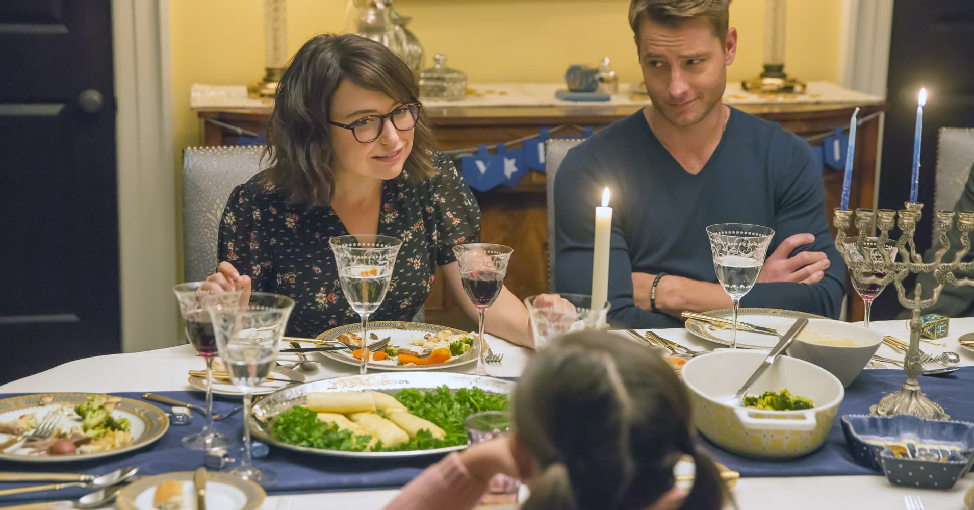 """A family dinner from TV show, """"This is Us,"""" featuring Milana Vayntrub as Sloane and Justin Hartley as Kevin."""