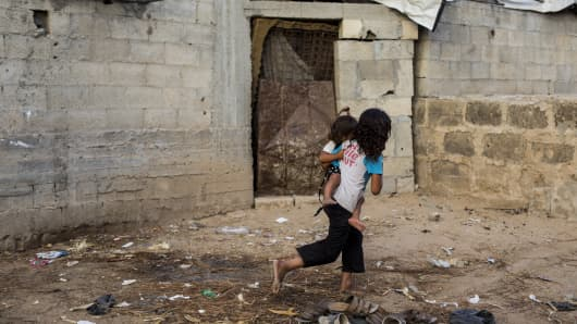 Palestinian refugee kids seen playing outside their temporary home in the northern Gaza Strip town of Beit Lahiya.
