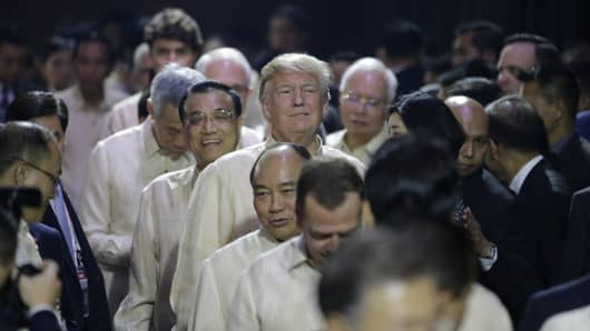U.S. President Donald Trump smiles in front of Chinese Premier Li Keqiang as they line up  to enter the Special Gala Celebration of the 50th Anniversary of ASEAN in Manila on November 12, 2017.