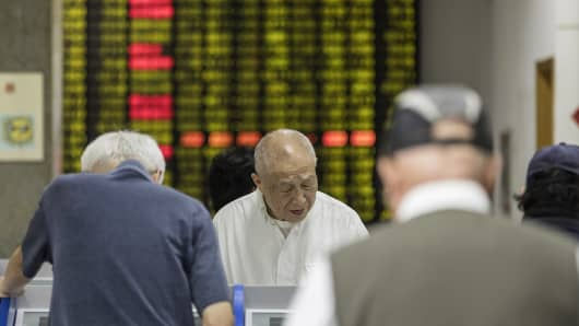 Investors stand at trading terminals in front of an electronic stock board at a securities brokerage in Shanghai, China, on Wednesday, May 30, 2018.