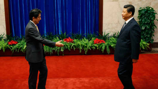 Japanese Prime Minister Shinzo Abe stretches out to Chinese President Xi Jinping during a 2014 meeting in Beijing, China.