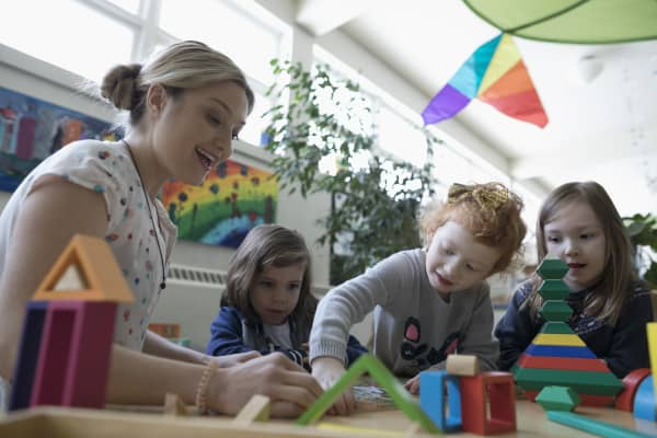 Preschool teacher and girl students playing with building blocks in classroom