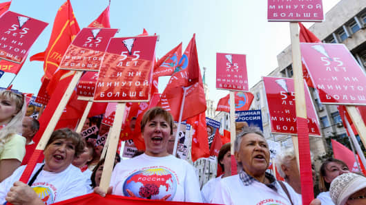 Russian Communist party supporters carry a banner reading '55 - and no minute more' as they take part in a rally against the government's proposed reform hiking the pension age in Moscow on September 2, 2018.