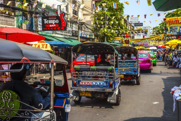 Tuk-tuks drive down Khao San Road in Bangkok, Thailand.