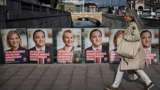 A woman walks next to election posters of the leader of the Social Democrats and Swedish Prime Minister Stefan Loefven, Swedish Minister for Finance Magdalena Andersson (L) and Sweden's Foreign Minister Margot Wallstrom on September 1, 2018 in Stockholm.