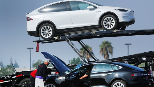 Newly manufactured Tesla vehicles are placed on transport trailers from a large inventory of newly made vehicles in Burbank, California, August 24, 2018.