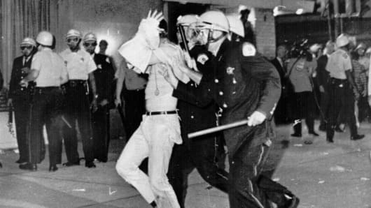 An Aug. 28, 1968 file photo shows a demonstrator with his hands on his head is led by Chicago Police down Michigan Ave. during a confrontation with police and National Guardsmen who battled demonstrators near the Conrad Hilton Hotel, headquarters for the Democratic National Convention.