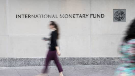 Pedestrians walk past the International Monetary Fund headquarters in Washington, D.C.