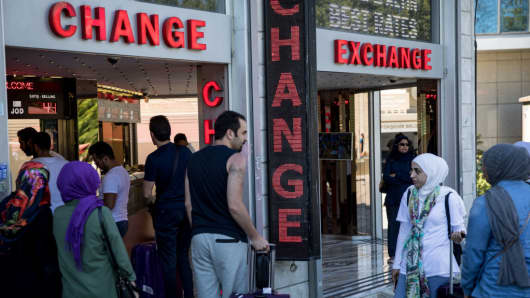 People change money at a currency exchange shop on August 14, 2018 in Istanbul, Turkey.