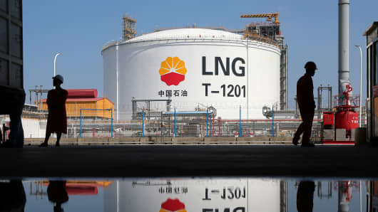 A liquified natural gas (LNG) storage tank and workers are reflected in water at PetroChina's receiving terminal at Rudong port in Nantong, China, September 4, 2018.