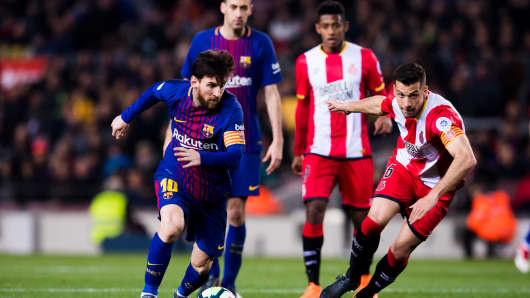 Lionel Messi of FC Barcelona runs with the ball next to Alex Granell of Girona FC during the La Liga match between Barcelona and Girona at Camp Nou on February 24, 2018 in Barcelona, Spain.