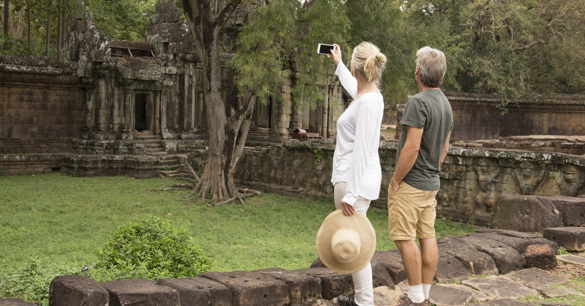 Mature couple take photo of temples and jungle, Angkor Wat