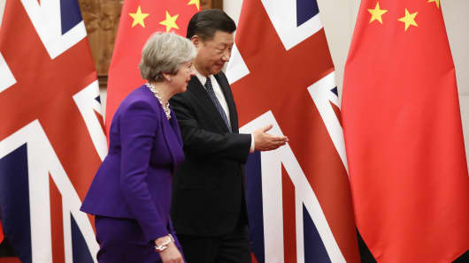 Chinese President Xi Jinping gestures the way to Britain's Prime Minister Theresa May ahead of their meeting in Beijing on February 1, 2018.