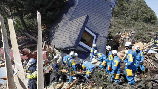 Rescue workers search for survivors from a house damaged by a landslide caused by an earthquake in Atsuma town, Hokkaido, Japan on September 6, 2018.