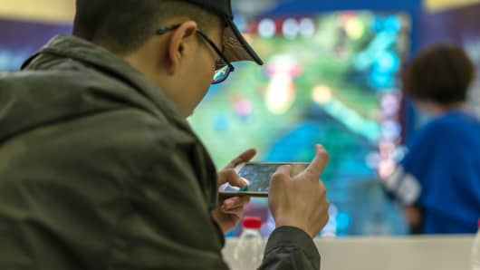 """Young players compete in a battle match of the mobile game """"Honor of Kings."""""""