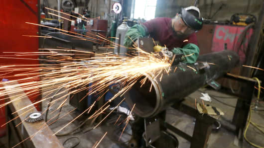 A man using an angle grinder on a steel piece at a metal fabrication company on August 7, 2018 in Orange County, New York.