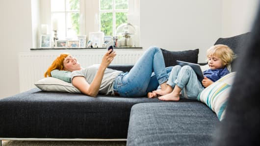 Mother and little son relaxing together on the couch with cell phone and tablet