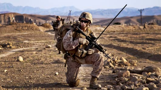 Marines pause during a dismounted patrol with Afghan National Civil Order Policemen during a training mission in Kajaki district, Helmand province, Afghanistan, April 28, 2013.