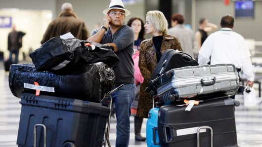 Travelers walk with their baggage at O'Hare International airport in Chicago.