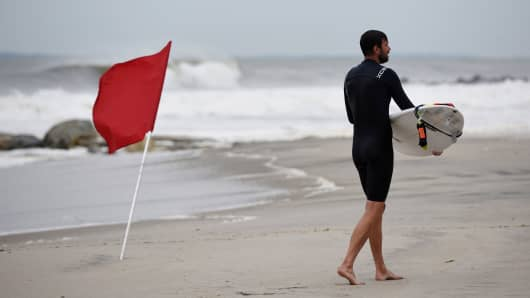 Aaron Austin heads in from a day of surfing at Rockaway Beach in Queens, New York on Labor Day where red flags warned of dangerous conditions due to post-tropical cyclone Hermine which tracked off the east coast of the U.S. September 5, 2016.