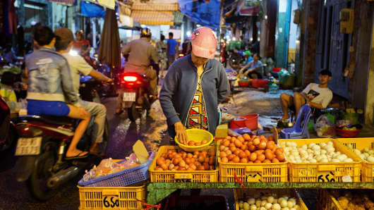 Motorcyclists pass vendors selling food in a market at night in Ho Chi Minh City, Vietnam, on Wednesday, June 20, 2018.