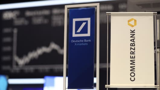 Banners of Deutsche Bank and Commerzbank are pictured in front of the German share price index, DAX board, at the stock exchange in Frankfurt, Germany.