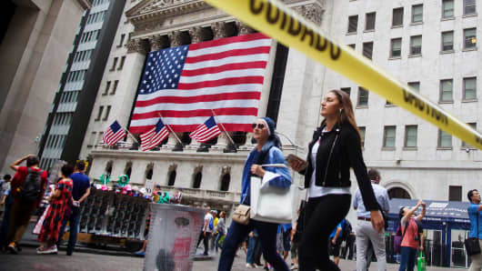 Pedestrians walk in front of the New York Stock Exchange (NYSE) in New York.