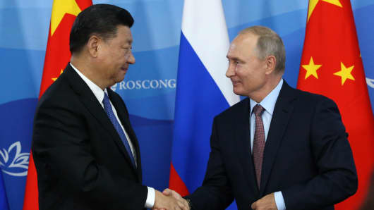 Russian President Vladimir Putin (R) greets Chinese President Xi Jinping (L) during their meeting at the Eastern Economic Forum on September 11, 2018.